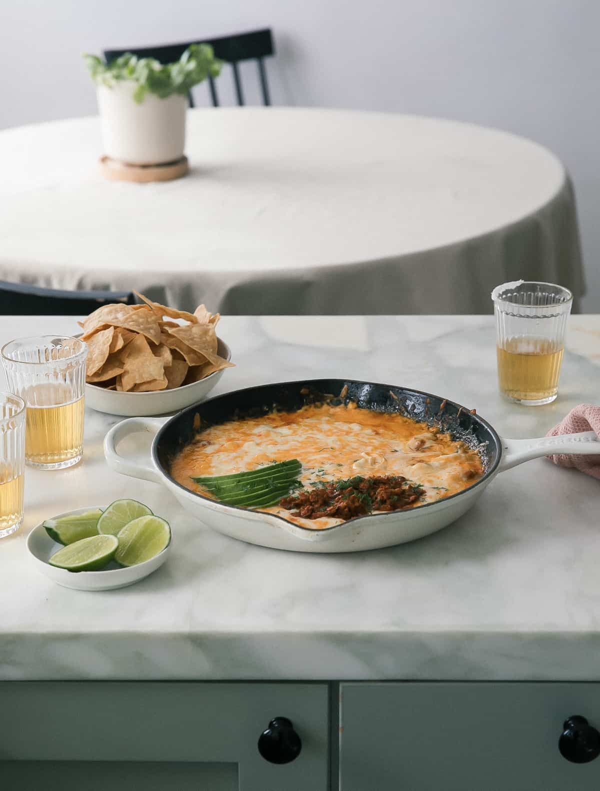 skillet of queso fundido topped with chorizo and avocado