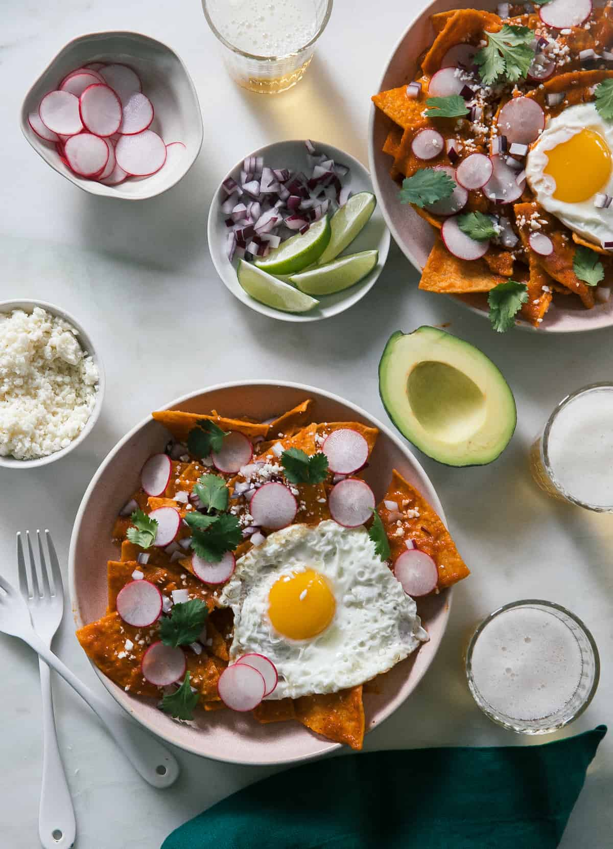 Two found blate of Chilaquiles with radishes, limes and avocado