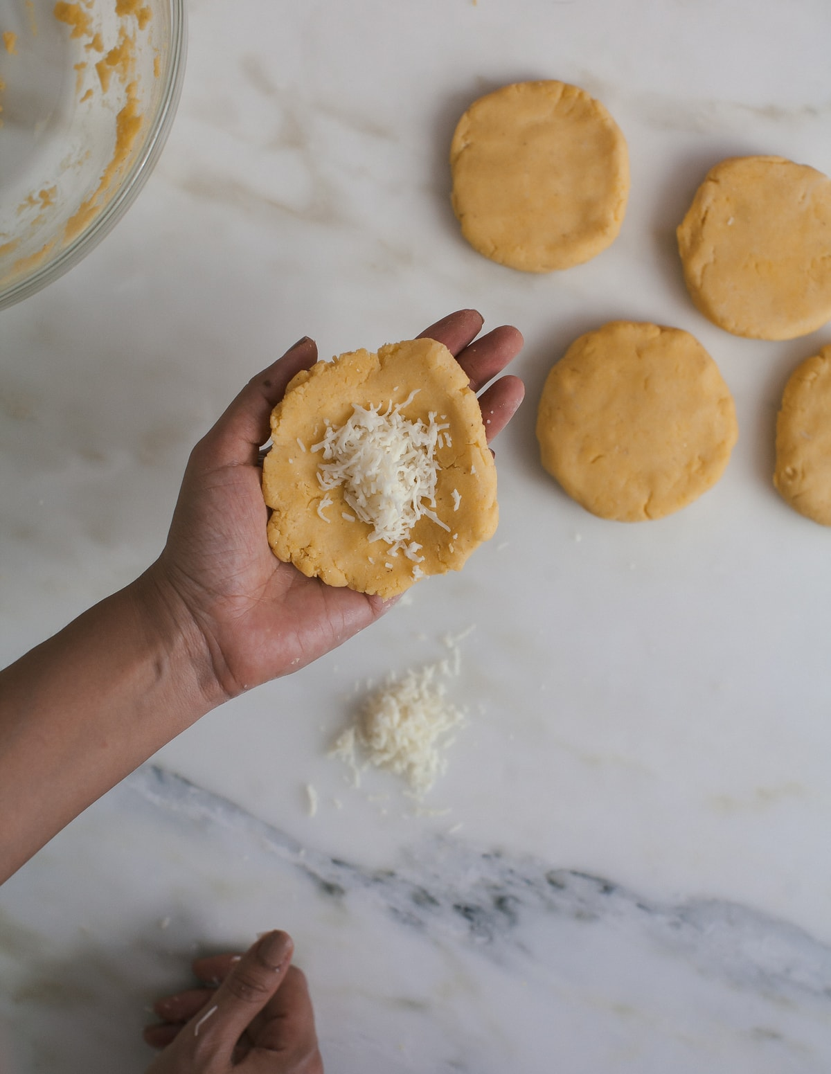 Arepas dough being stuffed with cheese