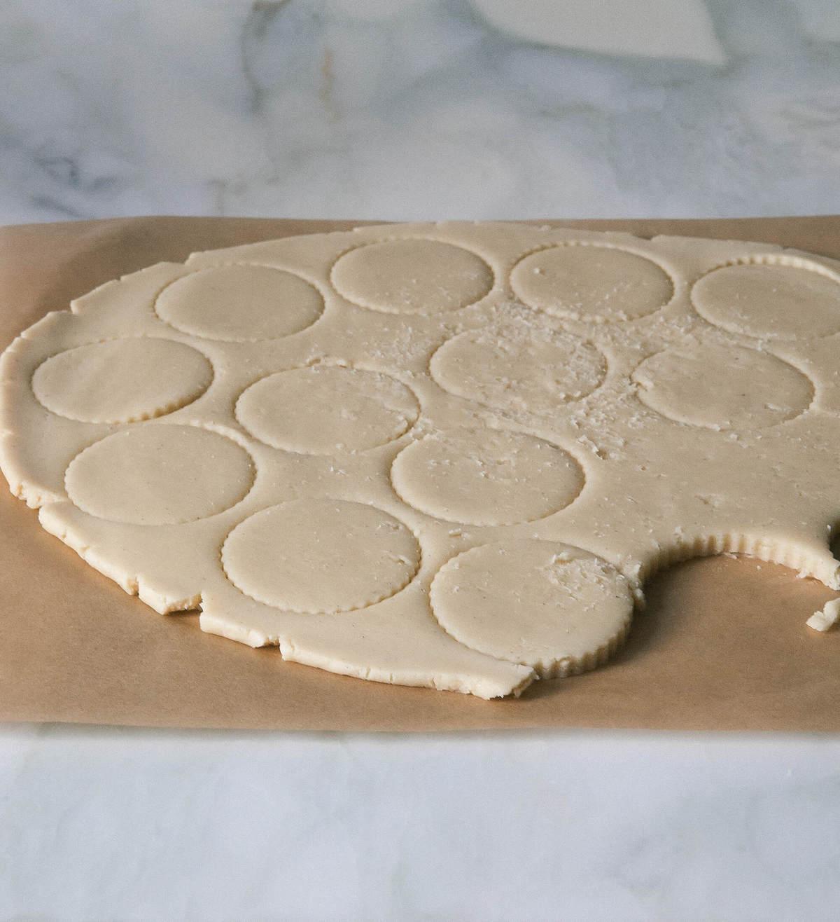 alfajores dough being cut out on parchment