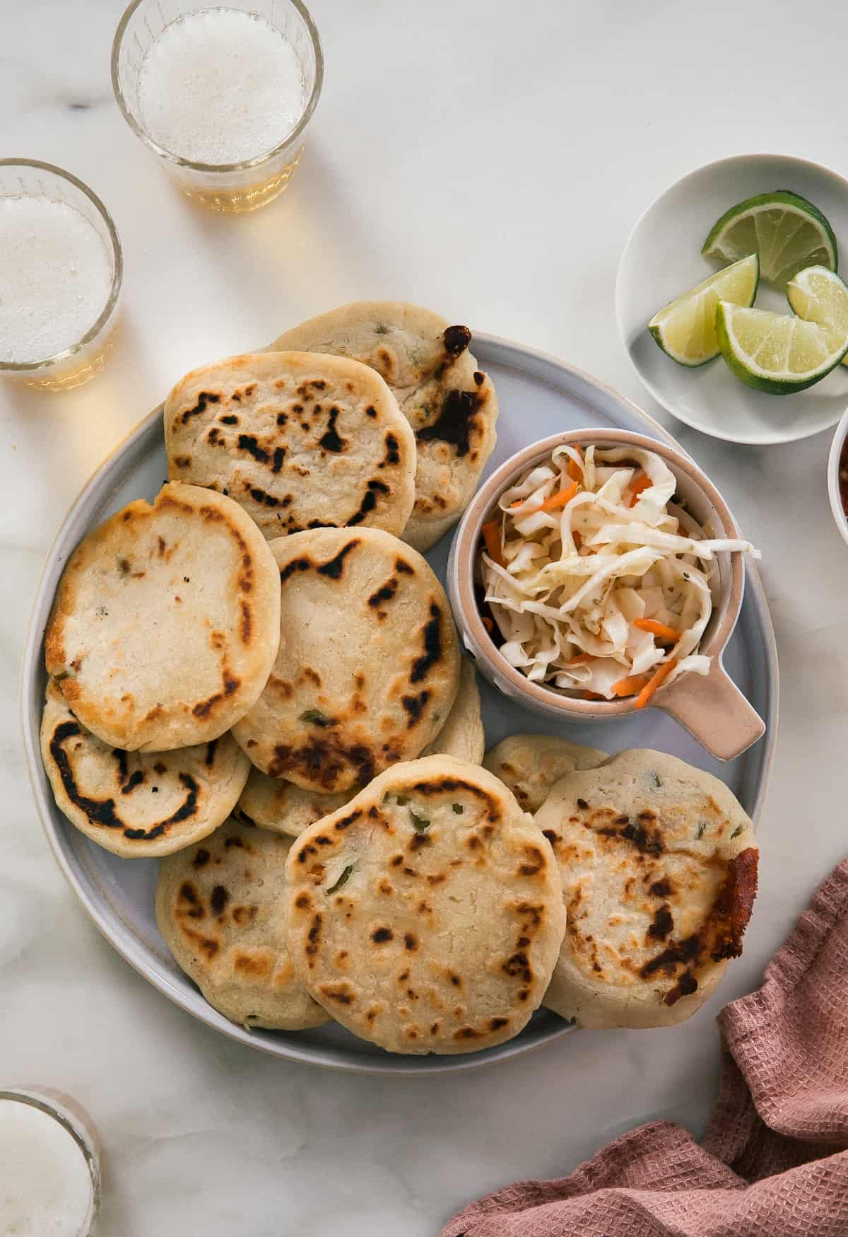 Pupusas on a round plate with curtido and limes