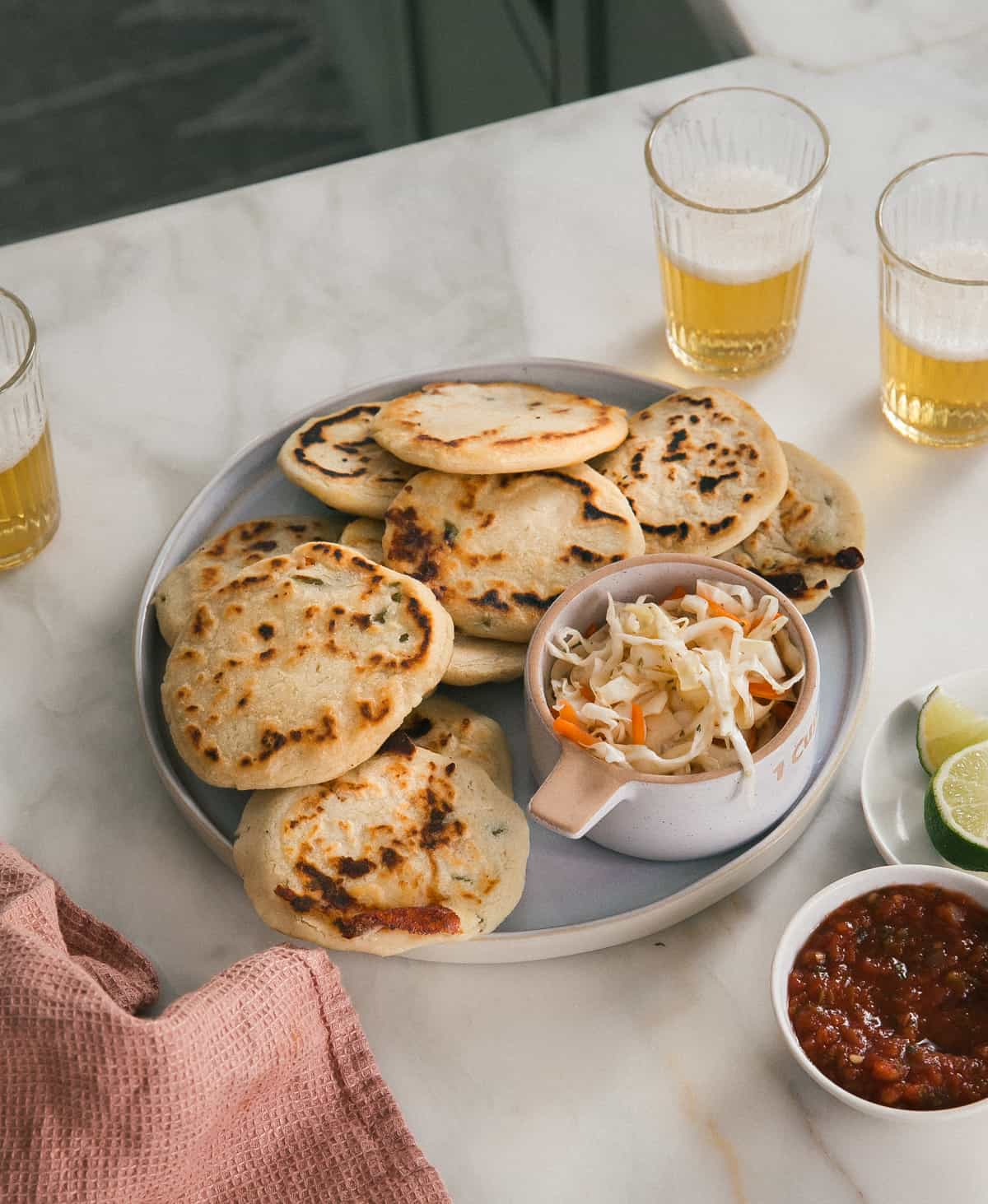 Pupusas on a plate surrounded by beer