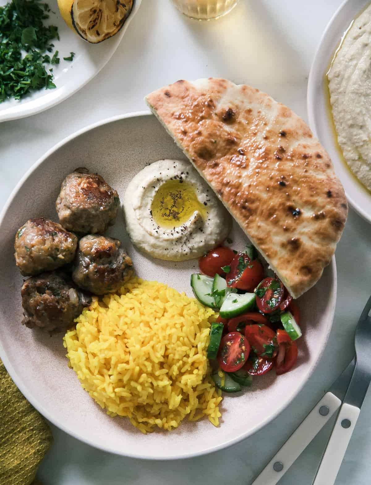 close up of lamb kofta bowl with rice, humus and pita