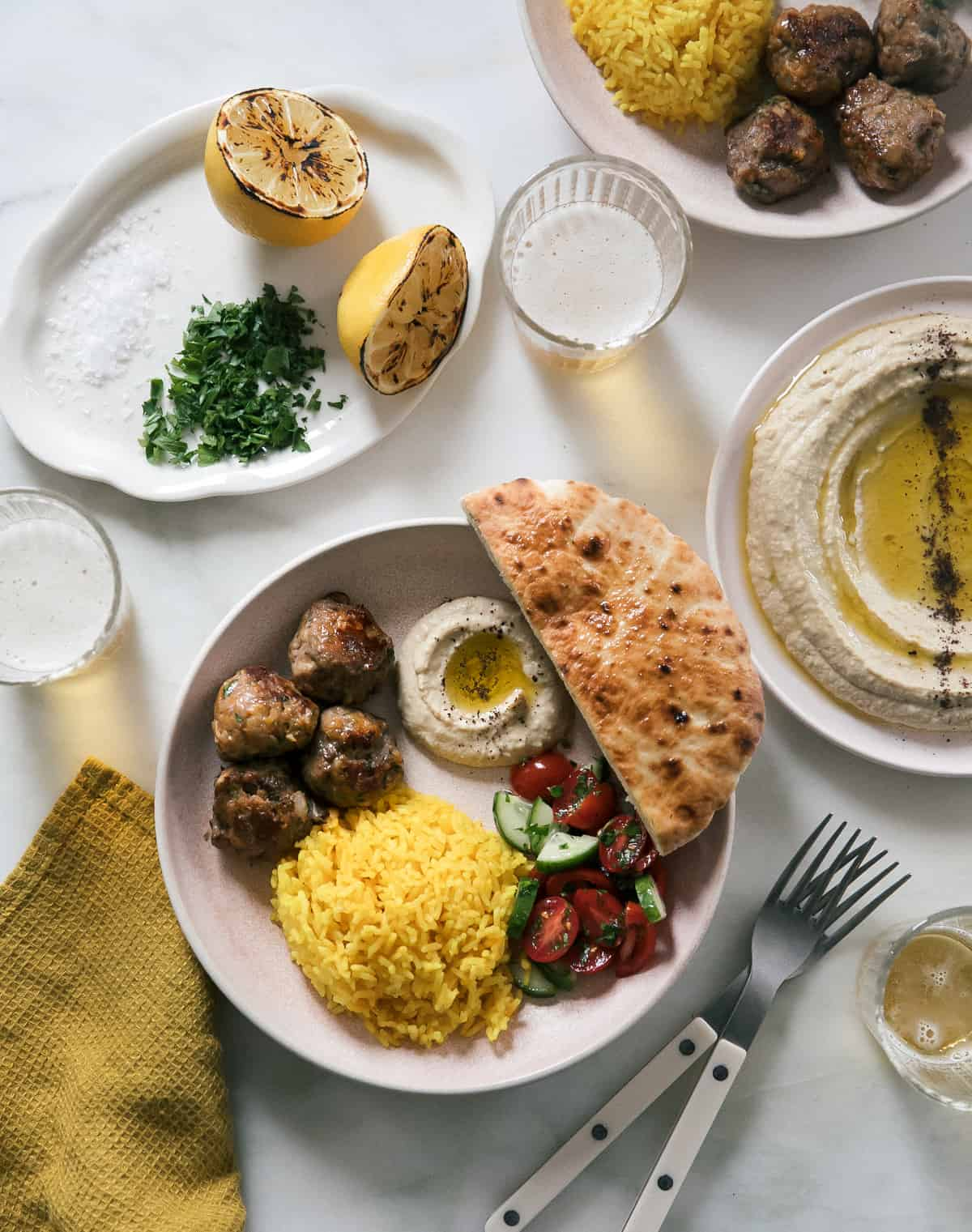 lamb kofta spread with hummus, pita, salad and yellow rice
