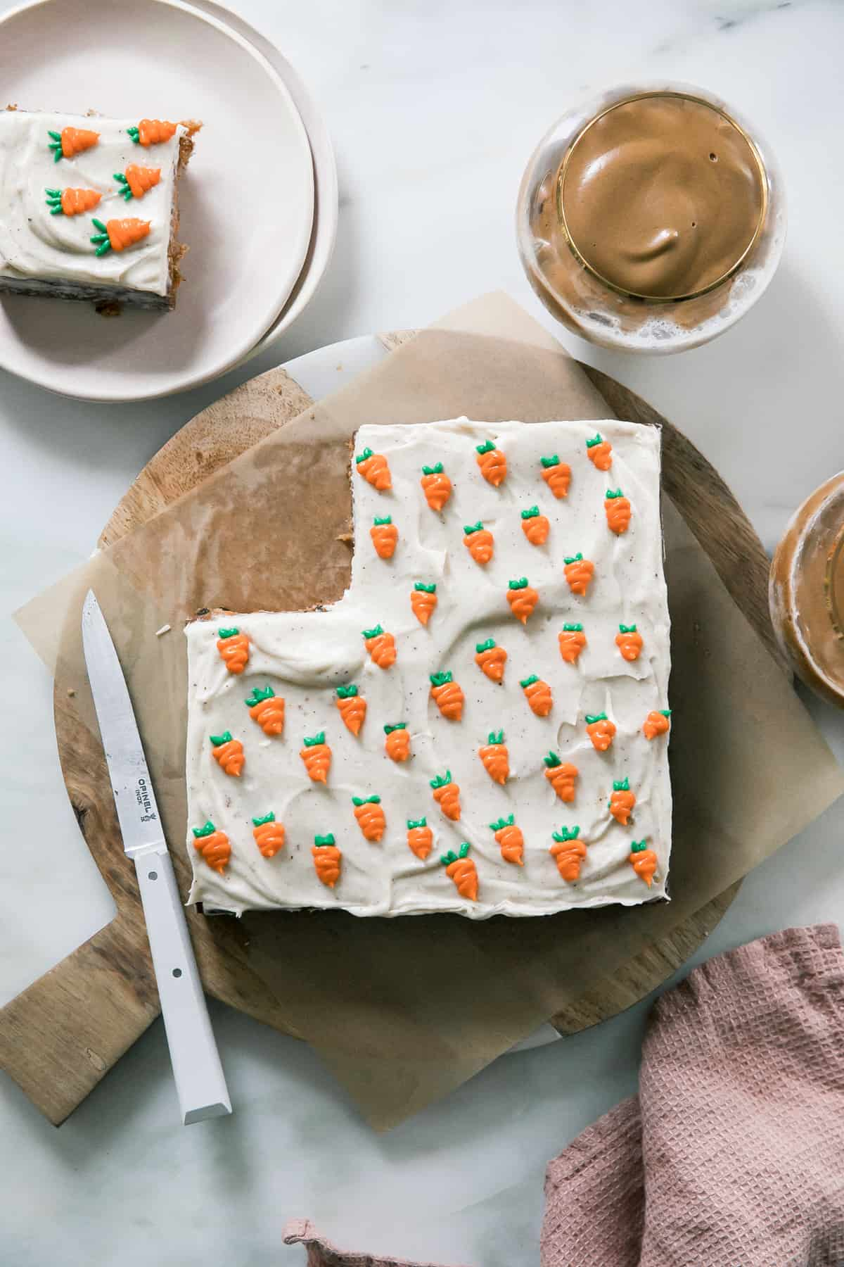 Carrot cake topped with piped on carrots on a cutting board