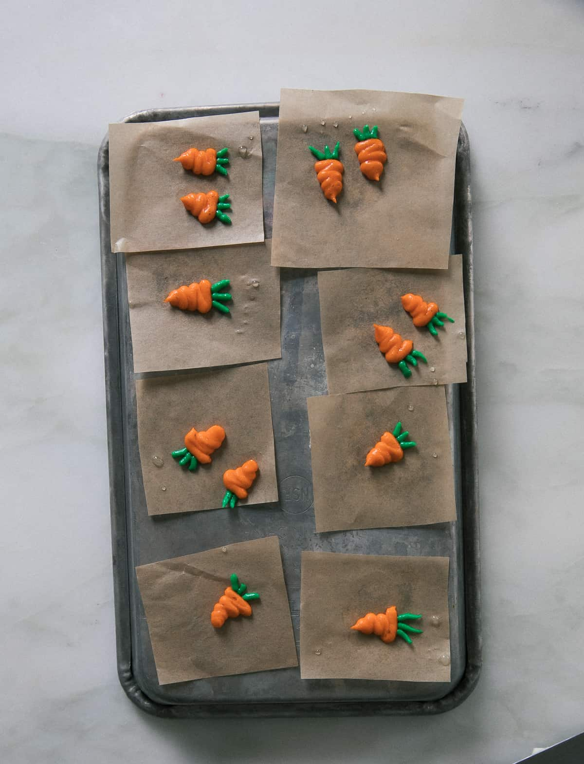 Piped mini carrots on pieces of parchment
