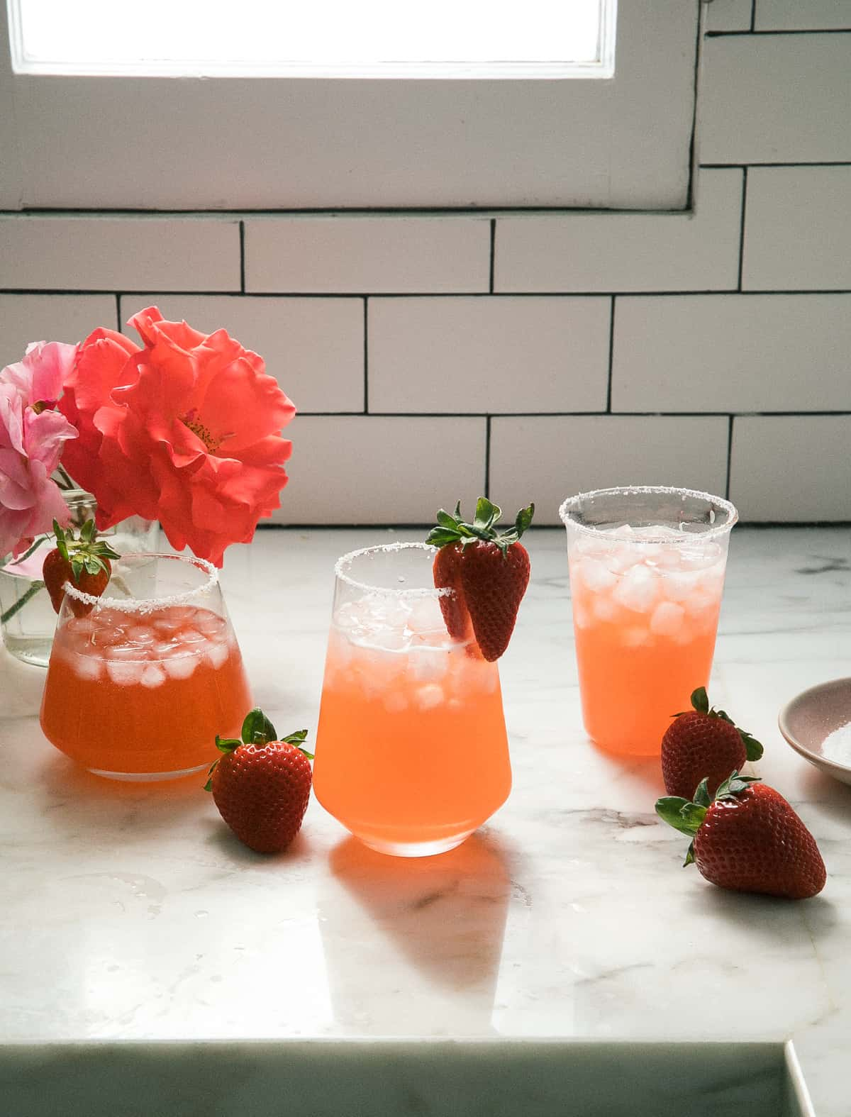 glasses of strawberry margaritas with strawberries and flowers