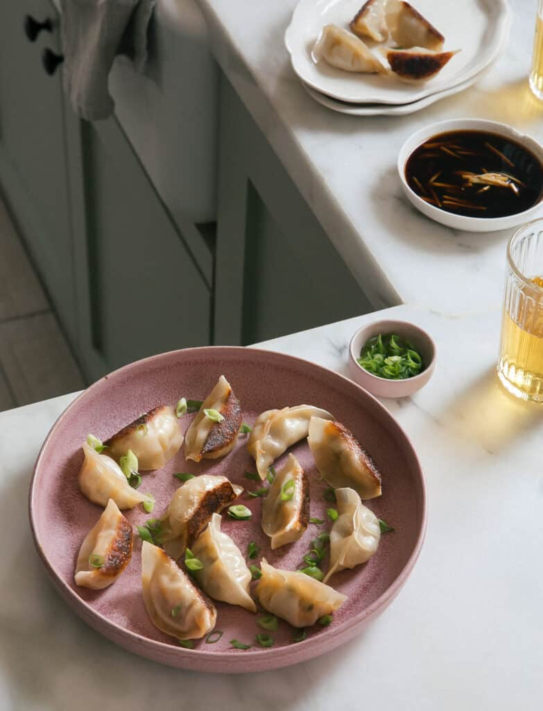 Potstickers on a plate with beer and dipping sauce