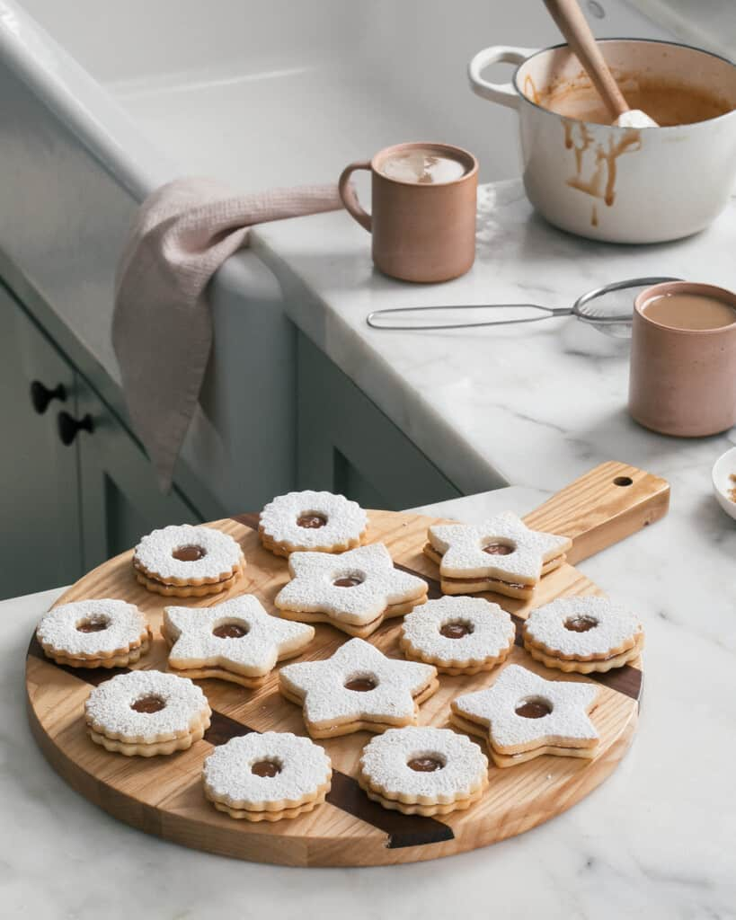 Salted Caramel Linzer Cookies on Counter with mugs
